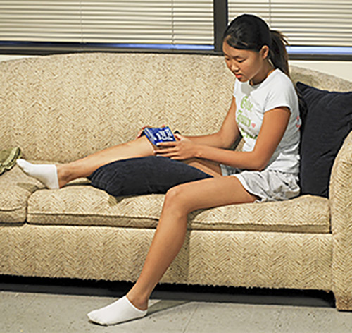 teen female sitting on sofa with ice pack on her knee.